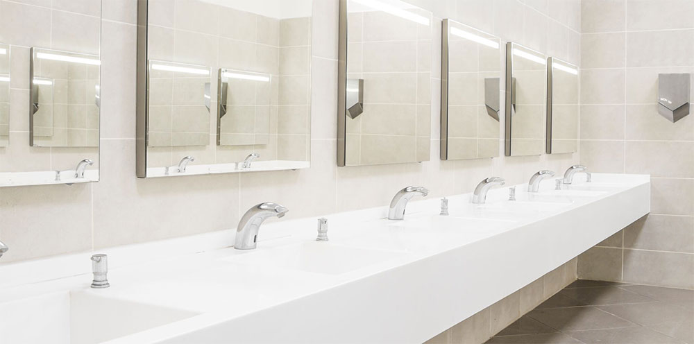A row of sinks in a hotel toilet